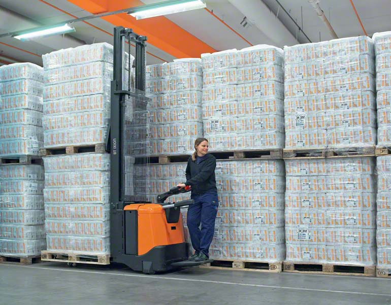 The operator rides the electric pallet truck to carry out warehouse tasks.