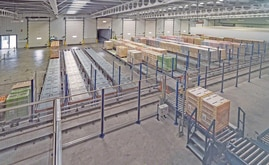 Two shuttles are tasked with depositing the pallets in one of the pallet flow channels available on the ground level