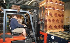For entry into the AS/RS pallet racking, lift trucks transport pallet loads to an induction station conveyor